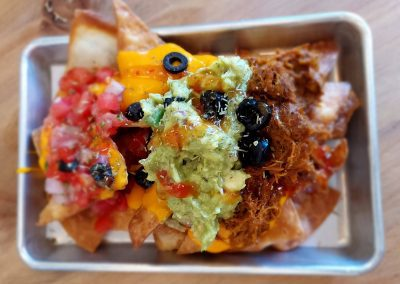 nachos with guacamole and salsa and olives